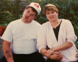 Picture of couple sitting, man making goofy faces.