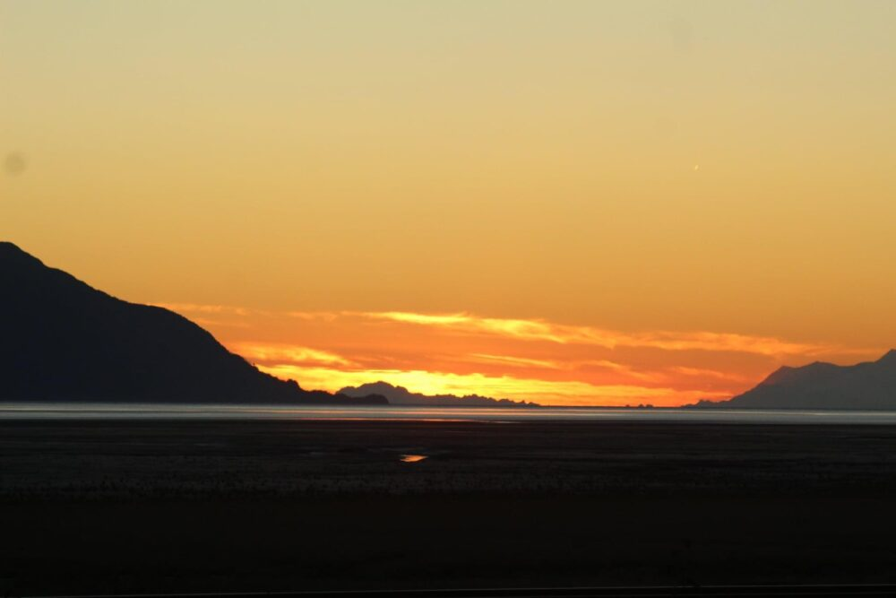 The Alaskan Outlaw podcast is broadcasted weekly from our studio in the land of the midnight sun. Returning home from a successful fishing trip on the Kenai River, the sunset over the Cook Inlet south of Anchorage, Alaska.